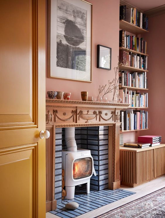 18 an eclectic living room with a rust-colored accent wall, a hearth in the fireplace, open shelves and a mini gallery wall