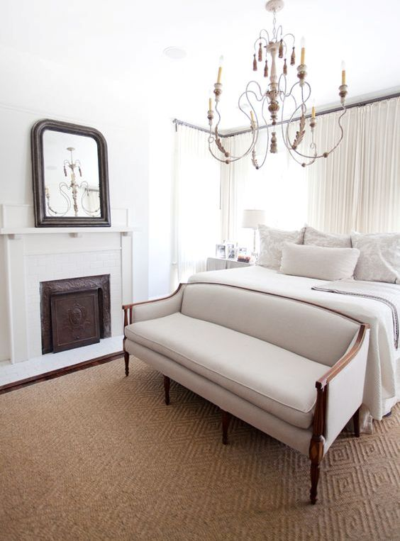 a refined creamy bedroom with a bed, a vintage loveseat at its foot, a vintage chandelier and a non-working fireplace