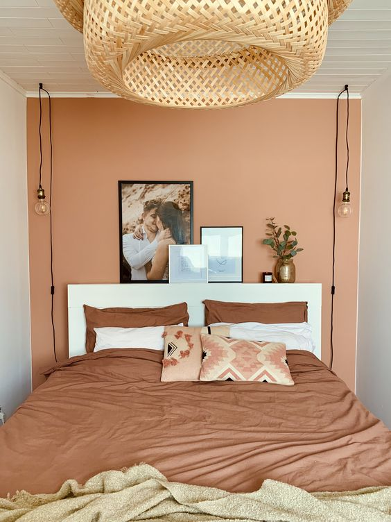 19 a small bedroom with a terracotta accent wall, a white bed and terracotta bedding and a large woven lamp