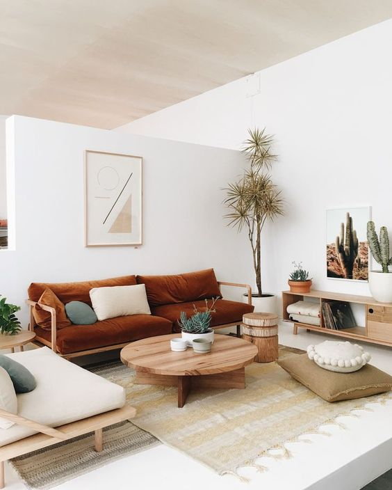 a boho living room with a rust colored sofa, neutral furniture, a round table, simple textiles and potted plants