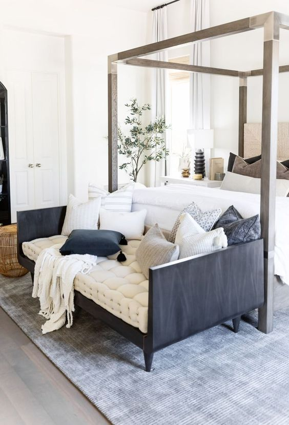 a refined farmhouse bedroom with a canopy bed, a contrasting sofa at the foot, potted plants and shiny touches