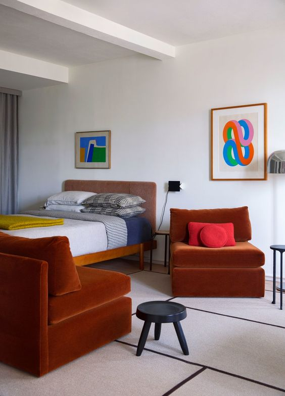 21 a bold bedroom with a wooden bed, terracotta chairs, bright art and color blocking catches an eye with each item