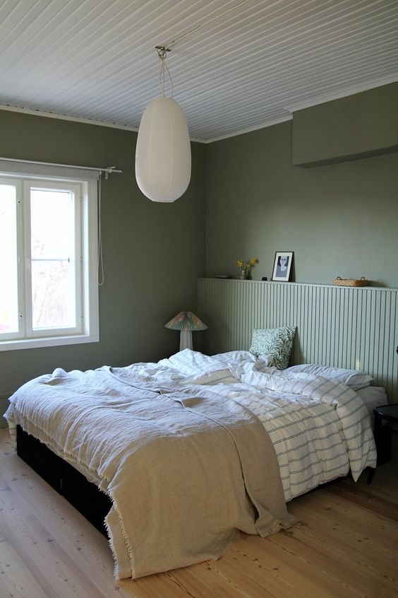 a paneled wood headboard that matches the walls in color makes the bedroom look airy and makes it visually larger