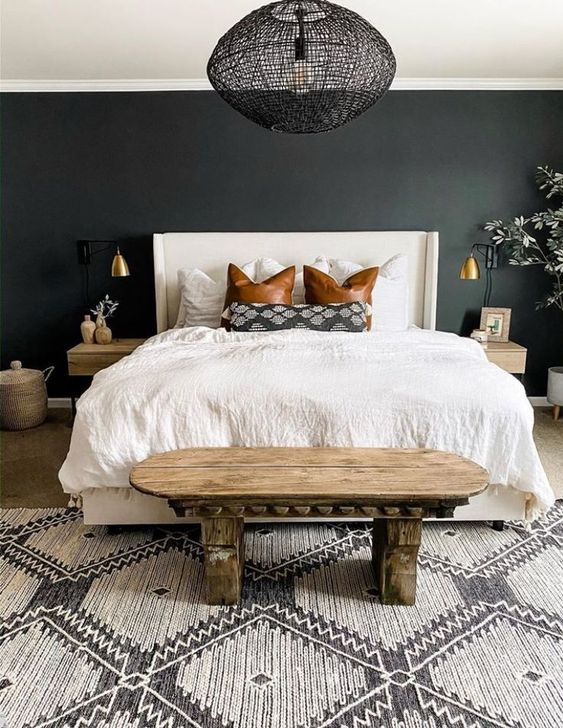 a stylish bedroom with a black accent wall, a white bed, a woven black lamp, a boho rug and a unique carved wooden bench