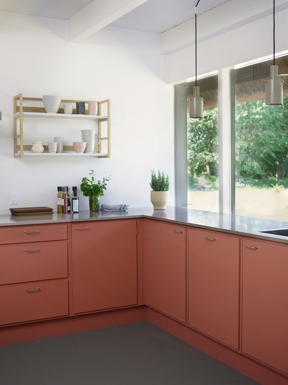 22 a bold rust-colored kitchen with grey countertops, an open shelf, green pendant lamps and potted greenery