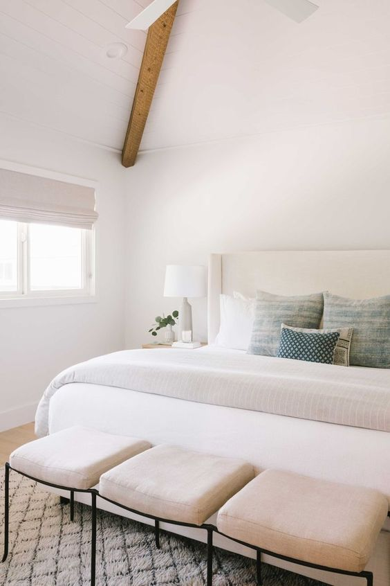 a soothing neutral bedroom with a creamy upholstered bed, creamy upholstered stools and wooden beams on the ceiling