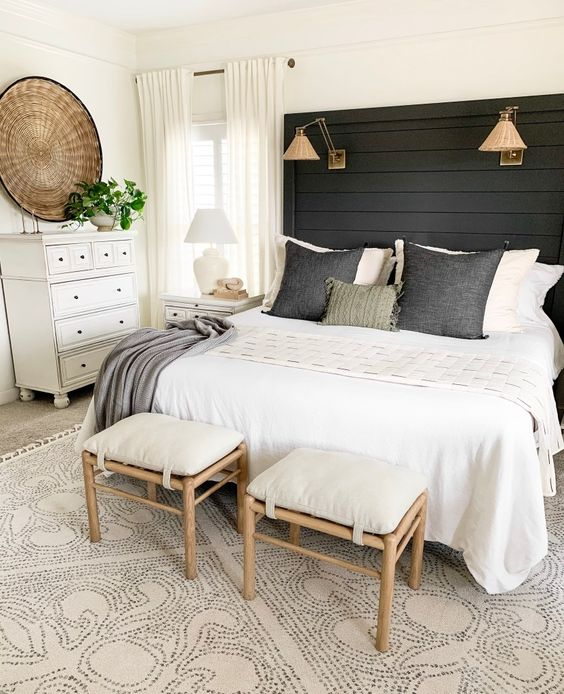 an extended black wooden headboard with additional sconces is a stylish and bold addition to the decor of the room
