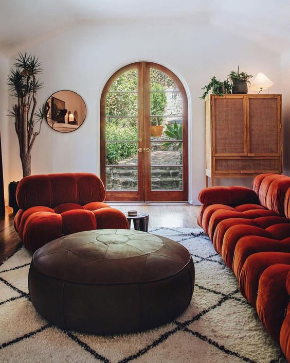 a catchy interior with bold rust colored seating furniture, a leather ottoman, a copper mirror and a rattan sideboard