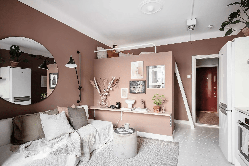 a pink studio apartment with a loft bed underneath a loft walk-in closet is a very smart solution to rock