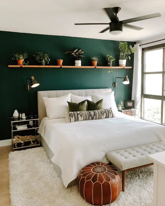 a stylish modern bedroom with a green accent wall, a creamy upholstered bed and a matching bench, a long shelf with potted plants