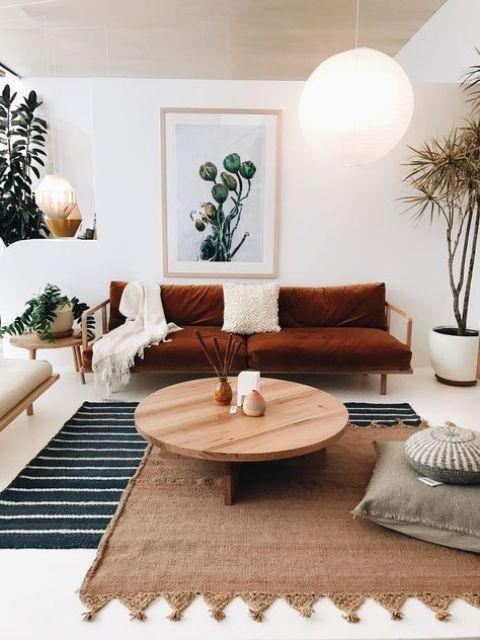 24 a neutral boho living room with a rust-colored sofa, layered rugs and pillows, a low round table and potted plants