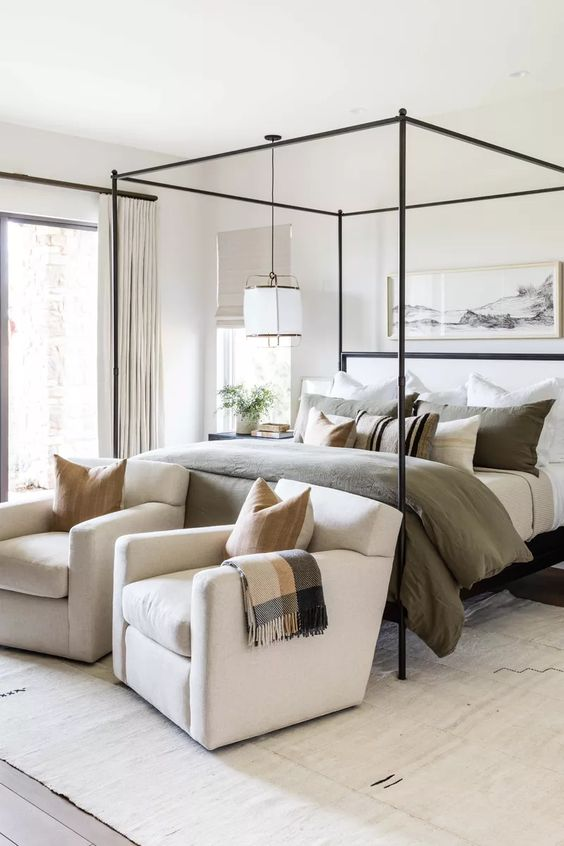 a super chic and cozy neutral modern bedroom with a canopy bed, a duo of upholstered chairs at the foot and a pendant lamp