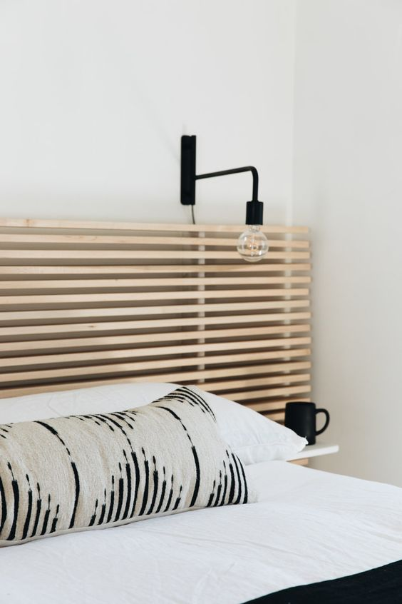 a stylish wooden slat headboard with a sconce over it and a floating nightstand is a chic contemporary idea