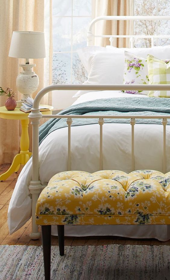 a vintage bedroom with a white metal bed, a yellow floral tufted bench, bright and neutral bedding and a yellow nightstand