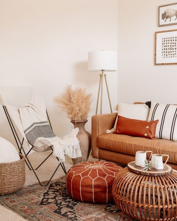 26 a neutral boho space with a tan leather sofa and a rust-colored ottoman, striped textiles, pampas grass and a wooden table
