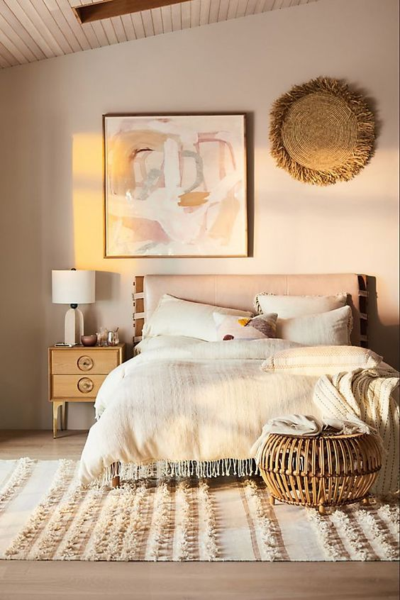 a warm-colored global bedroom with a boho feel, a bed wiht an upholstered headboard and a rattan ottoman at the foot