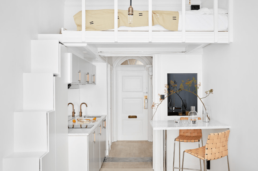 a white Scandinavian studio apartment with a loft bedroom, a small dining and kitchen space underneath