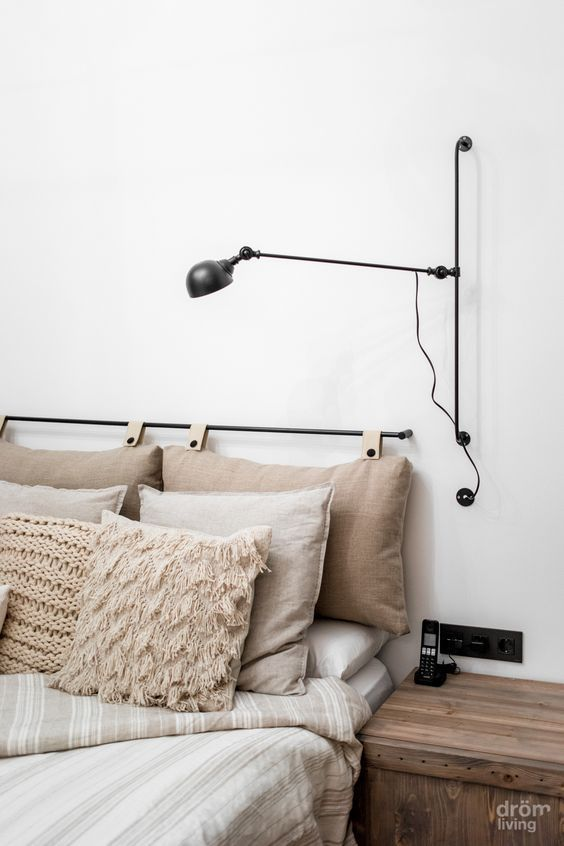 a cozy neutral bedroom with a lovely pillow headboard on a holder, a comfy sconce and a wooden nightstand