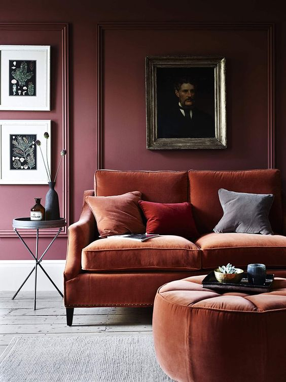 27 a refined and moody living room with a burgundy paneled wall, a gallery wall, a rust-colored sofa and an ottoman plus colorful pillows