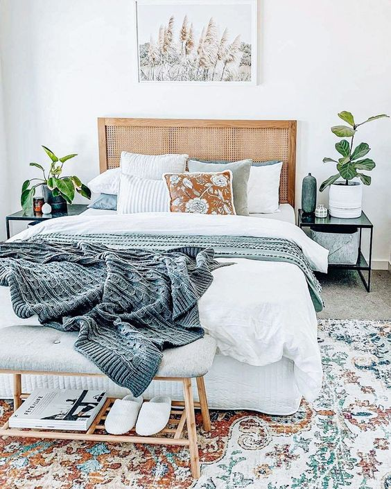 a welcoming boho bedroom with a bed with a cane headboard, an upholstered bench, potted plants and a cool rug