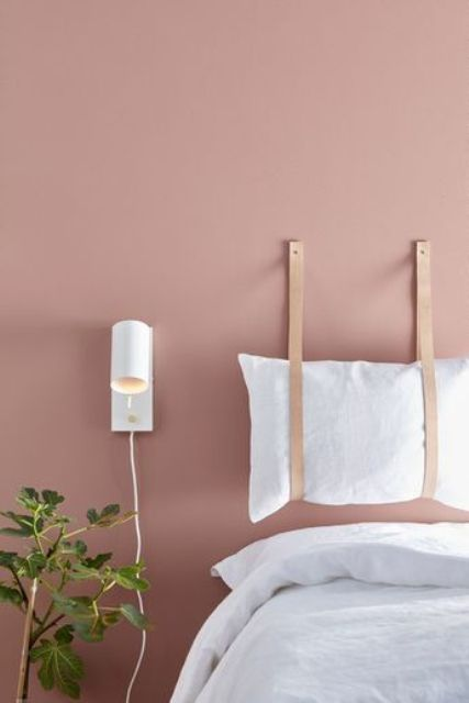 a lovely and simple pillow headboard suspended on leather straps is a very cool and fresh idea