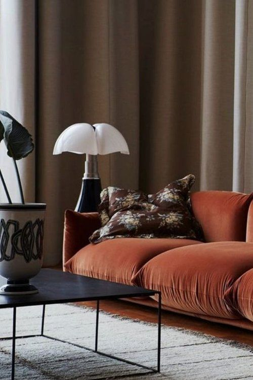 a refined living room with a burnt orange sofa, a floral pillow, a quirky lamp and a low table with a statement vase