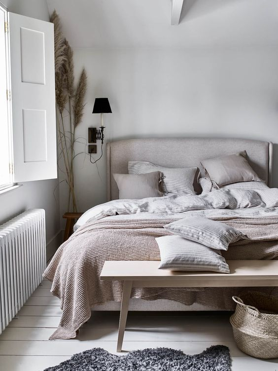 an ethereal and soothing bedroom in neutrals, with an upholstered bed, a blonde wood bench, vintage sconces and pampas grass