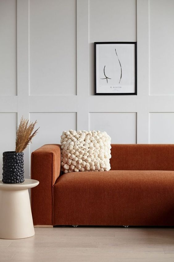 a refined modern space with off white paneled walls, a terracotta sofa, a pompom pillow and a matching vase
