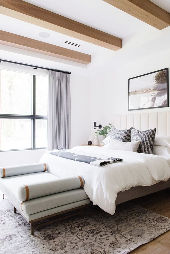 an exquisite and beautiful bedroom with wooden beams, a creamy upholstered bed, a chic daybed and neutral textiles