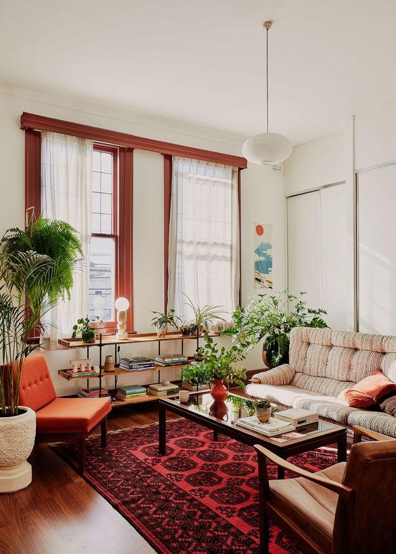 30 a chic boho living room with rust-colored window frames, a rust chair and pillows, a neutral sofa and chic leather chairs