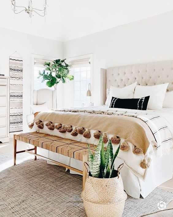 an inviting boho bedroom in neutrals, with a woven boho bench, pretty woven rugs on the wall