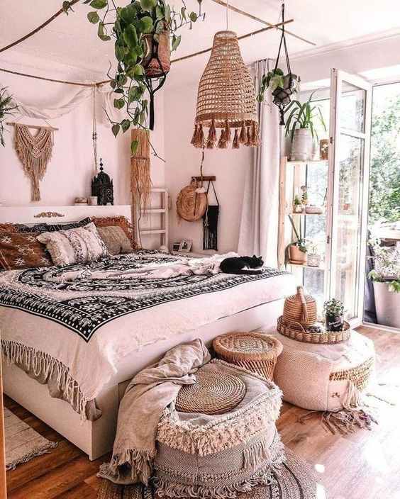 a beautiful boho bedroom with a canopy bed, a pendant lamp, rattan and fabric ottomans at the foot of the bed and potted plants