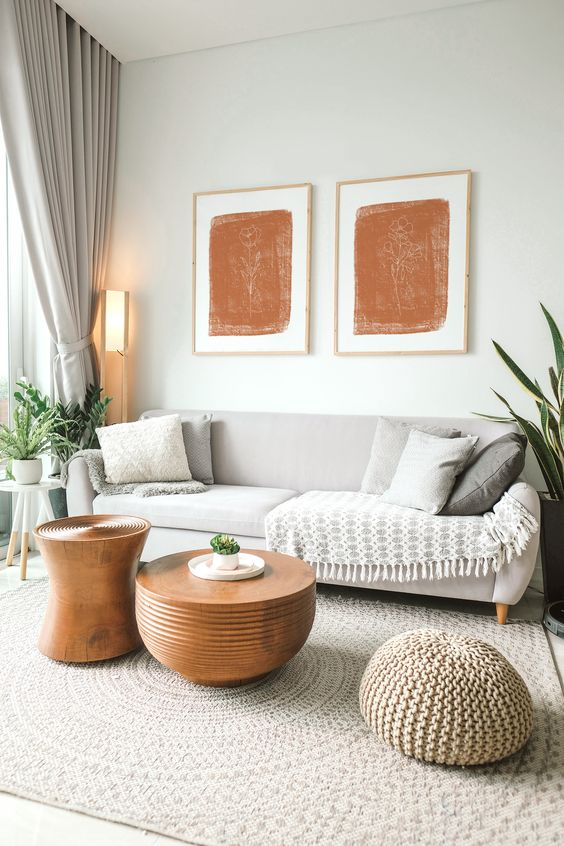 31 a lovely all-neutral living room in creamy and dove grey shades, with neutral pillows, potted plants, terracotta artworks and amber tables