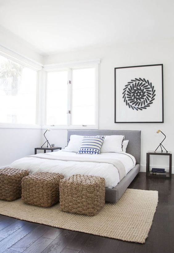 a stylish contemporary bedroom with a grey upholstered bed, a trio of woven poufs, a statement artwork over the bed