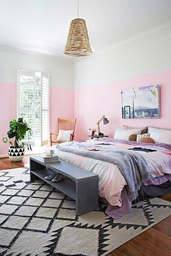 a bright bedroom with hot pink walls, a comfy bed, a grey storage bench and a woven pendant lamp