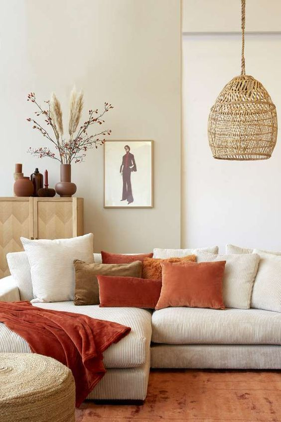 33 a neutral boho living room accessorized with bright rust and terracotta pillows and a woven pendant lamp is chic