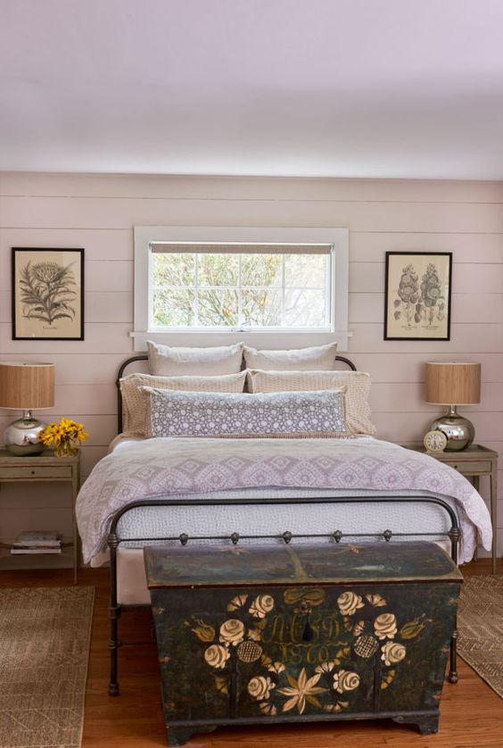 a farmhouse bedroom with olvie green nightstands, a forged bed and a vintage painted chest for storage