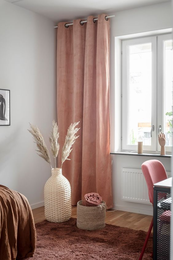 a warm colored space with a brown rug and a bedspread, a pink chair and rust colored curtains that add warmth here