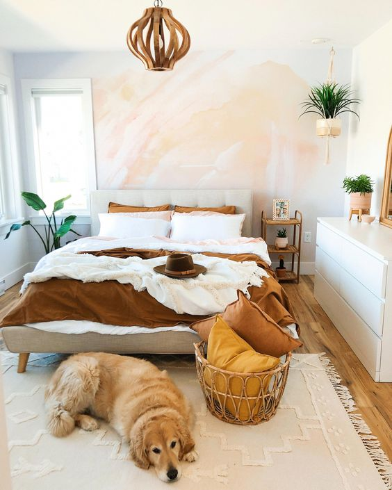 a gorgeous bedroom with a watercolor accent wall, a creamy upholstered bed, a rattan basket with pillows and a sleek dresser