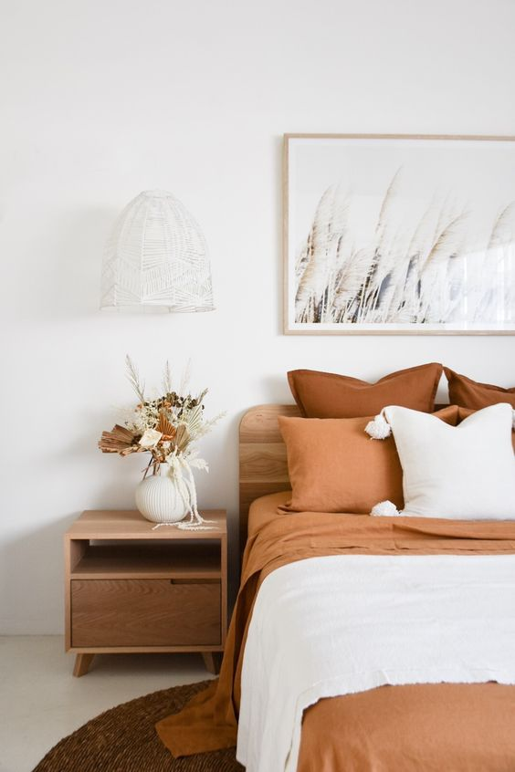35 an ethereal bedroom with light stained wooden furniture, rust-colored bedding, a white woven pendant lamp and dried leaves