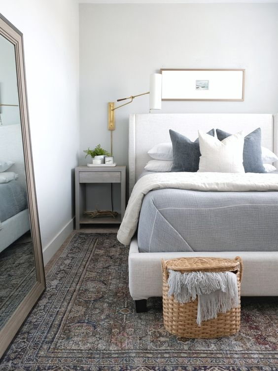 a neutral and pastel coastal bedroom with a creamy bed, grey nightstands, a basket with a blanket at the foot and a mirror