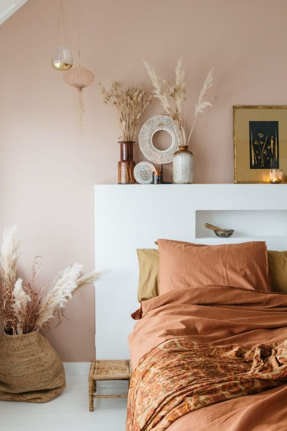36 an inviting boho bedroom with a pale brown wall, a bed with terracotta bedding, grasses in vases and candles is cool
