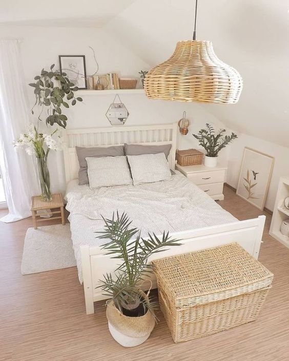 a neutral attic bedroom with a white bed, a large woven chest and a potted plant plus a woven pendant lamp