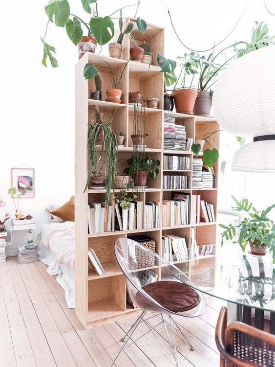 a cool storage space divider - a tall bookshelf - is a very functional and smart storage solution