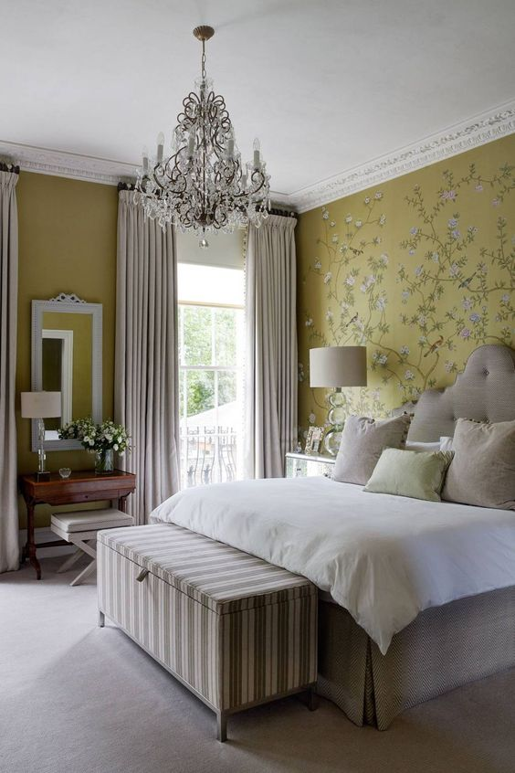 a Parisian chic bedroom with mustard wlals and a floral accent one, an upholstered bed, a crystla chandelier and a striped chest at the foot of the bed