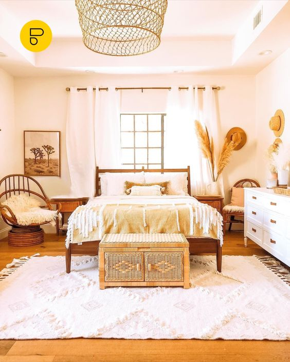 a pretty and warm-colored boho bedroom with wooden and rattan furniture, a beautiful boho chest at the foot and pampas grass