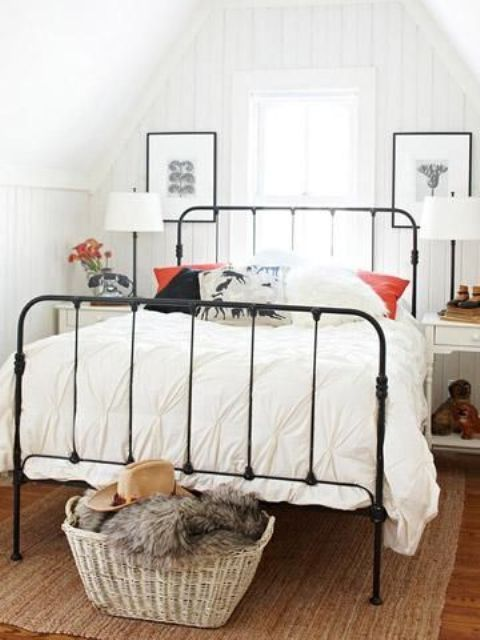 a small attic bedroom in neutrals, with a forged bed, white nightstands and a basket for storage