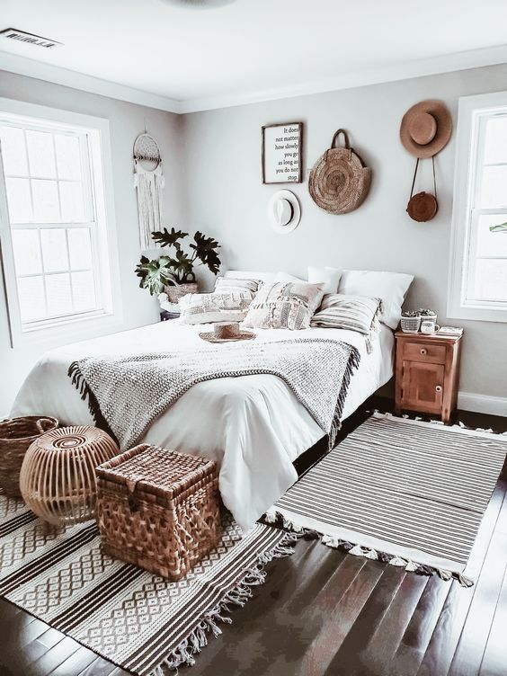 a beautiful neutral boho bedroom with a bed, a variety of baskets at the foot, hats and a bag on display