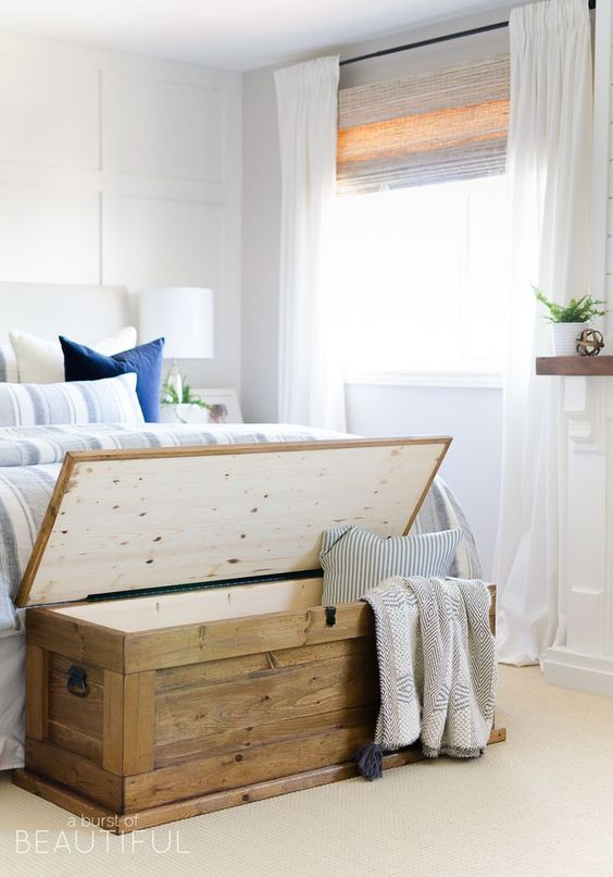 a white and blue coastal bedroom with an upholstered bed, striped bedding, a wooden chest for storage and potted plants