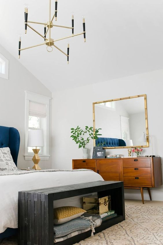 a stylish mid-century modern bedroom with a bold blue bed, a dark wooden storage bench, a chic dresser and a gilded frame mirror